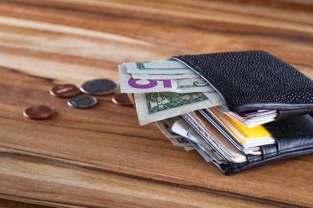 primo piano di un portafoglio con dollari americani sporgenti e cambiare su un tavolo di legno