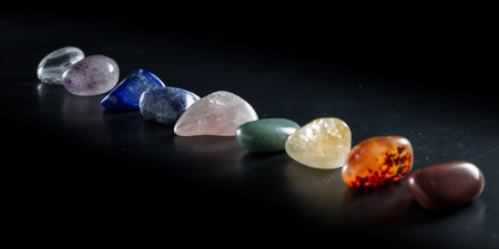 Chakra balancing stones arranged in order from upper to lower chakras Stock Photo