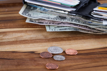 assigned: close up of a wallet with American Dollars sticking out and change on a wooden table Stock Photo