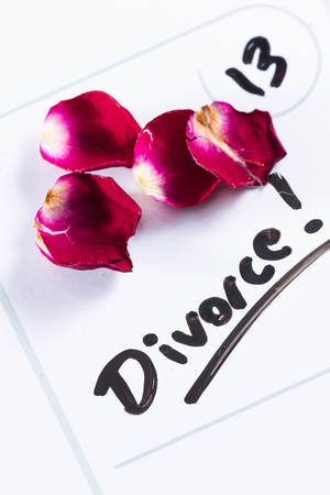 the word divorce hand written on a dry erase calendar with a dead rose next to it Stock Photo