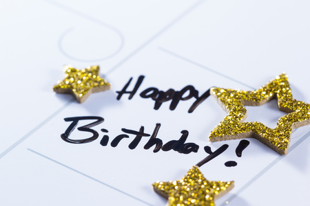 allocated on white: close up of a calendar with the words happy birthday written on it and then decorated with gold stars