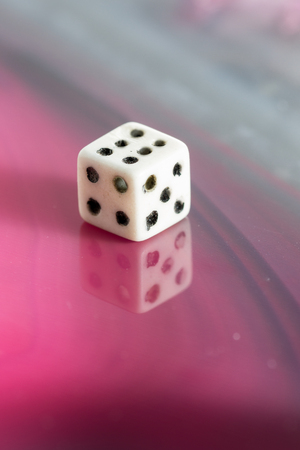 gambling stone: close up of an old used dice on a beautiful polished sliced stone Stock Photo