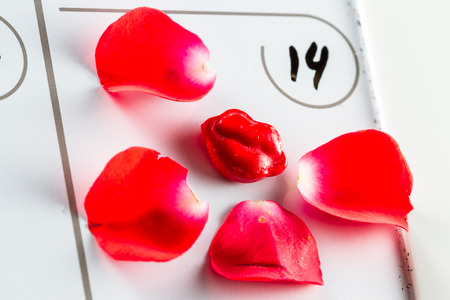 red condom: close up of a calendar with the number 14 written on it and red petals and lips as a concept for Valentines Day Stock Photo
