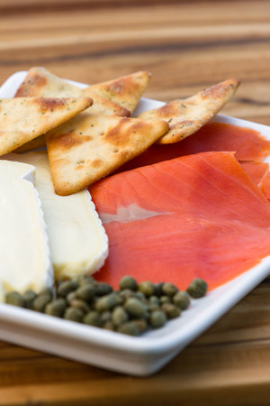 thin slices of smoked salmon served with brie cheese and salty crackers