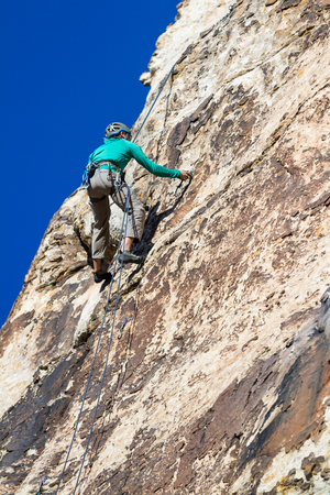 rockclimbing: young man repelling down a sandstone cliff in youth western Utah