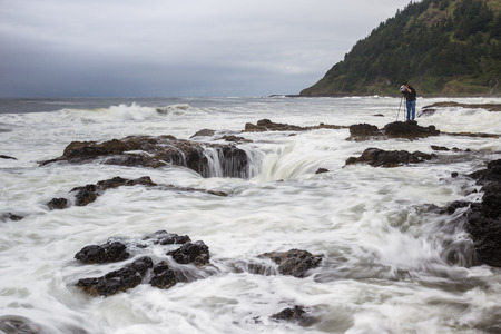 thor's: Cape Perpetua, Oregon - May 19 : young man standing on lava rock as the tide comes in, waiting for the perfect conditions to capture Thors Well, May 17 2015 Cape Perpetua, Oregon.