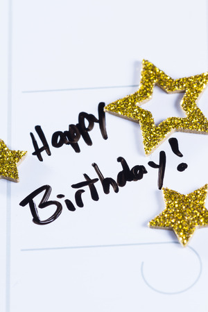 dry erase board: close up of a calendar with the words happy birthday written on it and then decorated with gold stars