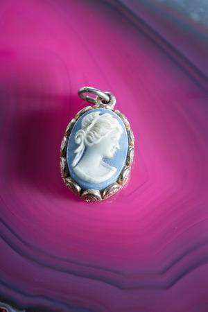 cameo: close up of a beautiful cameo on a vivid pink polished stone
