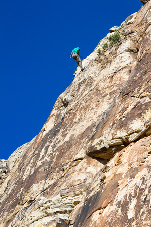 strenuous: young man repelling down a sandstone cliff in youth western Utah