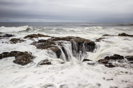 feature: Thors Well, a feature in the Oregon coast where the water seems to drain down a lava rock sinkhole Stock Photo