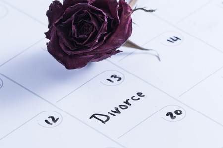 dry erase: close up concept image for a divorce using a dry erase calendar and a dried dead rose Stock Photo