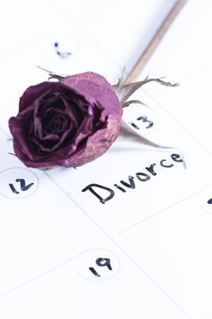 dry erase board: close up concept image for a divorce using a dry erase calendar and a dried dead rose Stock Photo