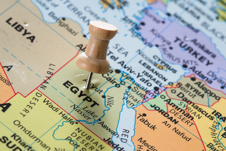 imaginary line: close up of the word Egypt on a world map marked with a push pin