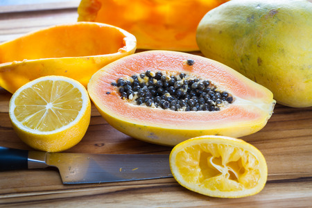 enzymes: close up of a papaya cut in half on a wooden cutting board served with a sliced lemon