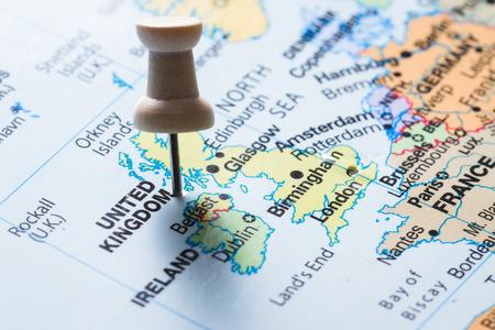 푸시 핀으로 표시된 영국에 초점을 맞춘 세계지도 닫습니다