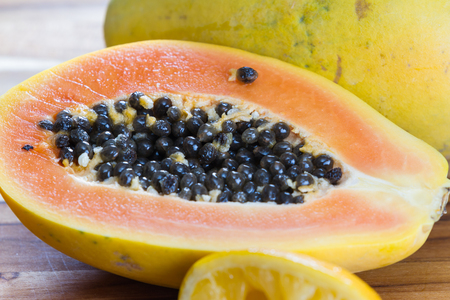 slimy: close up of a papaya cut in half revealing the meat and a pile of dark slimy seeds Stock Photo