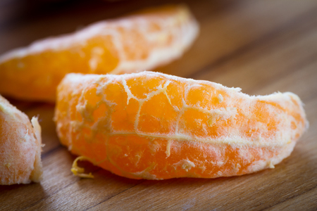enzymes: close up of a small orange or tangerine on a wooden cutting board