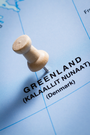 imaginary line: close up of a map focused on greenland with a push pin