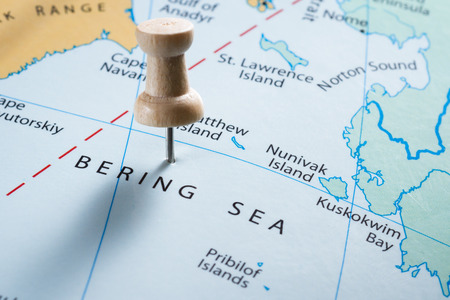 marking up: close up of  map with the words Bering Sea in focus with a push pin marking the spot