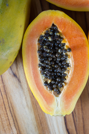 enzymes: close up of a papaya cut in half revealing the meat and a pile of dark slimy seeds Stock Photo