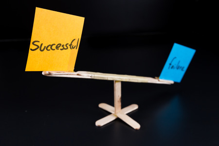 low self esteem: concept of duality using sticky notes with antonyms on a hand made sea saw on a dark background Stock Photo