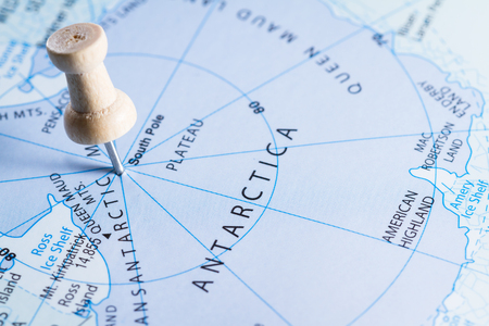 marking up: close up of  map with the word Antarctica in focus with a push pin marking the spot