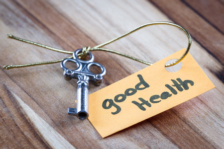 positiveness: concept for a happy healthy life using an old decorative key and a hand written tag attached by a golden cord