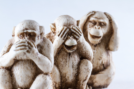 close up of hand small statues with the concept of see no evil, hear no evil and speak no evil. Stock Photo