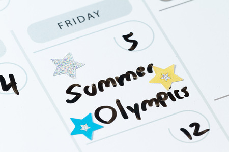 summer olympics: close up of a daily planner or calendar with a hand written message for a celebration or holiday like the beginning of the summer Olympics