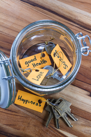 require: concept image using hand written tags and and old jar with the keys to life in it Stock Photo