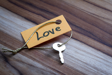 positiveness: concept for a happy loving life using an old decorative key and a hand written tag attached by a golden cord