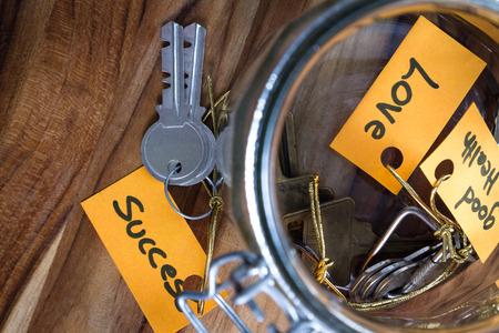 concept afbeelding met handgeschreven tags en en oude pot met de sleutels tot leven in het Stockfoto