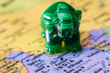 adn: view of a world map with india in focus adn a small jade elephant