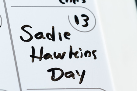 masses: close up of a daily planner or calendar with a hand written message. Sadie Hawkins day is an American Folk event, in the premise where females ask masses for a date or dance,