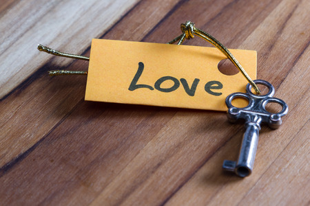 finding love: concept for a happy loving life using an old decorative key and a hand written tag attached by a golden cord