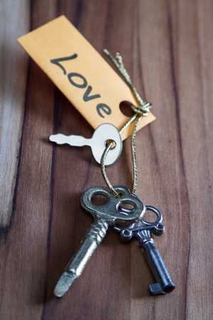 positiveness: concept for a happy loving life using old decorative keys and a hand written tag attached by a golden cord Stock Photo