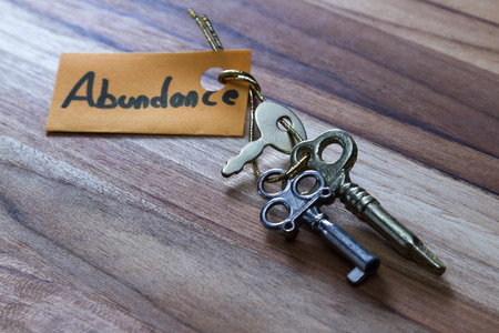 abundant: concept for a happy abundant life using old decorative keys and a hand written tag attached by a golden cord