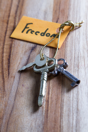 concept for a happy free life using old decorative keys and a hand written tag attached by a golden cord Фото со стока