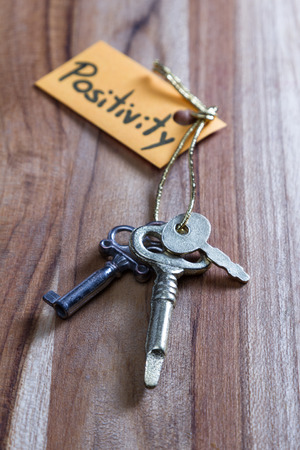 concept for a happy positive life using old decorative keys and a hand written tag attached by a golden cord Фото со стока