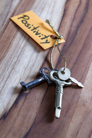 concept for a happy positive life using old decorative keys and a hand written tag attached by a golden cord Stock Photo