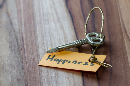 positiveness: concept for a happy life using an old decorative key and a hand written tag attached by a golden cord