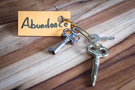 concept for a happy abundant life using old decorative keys and a hand written tag attached by a golden cord