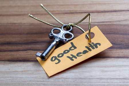 findings: concept for a happy healthy life using an old decorative key and a hand written tag attached by a golden cord