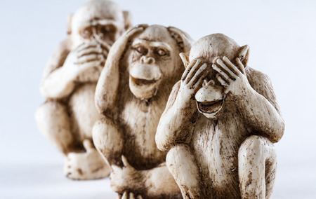 see: close up of hand small statues with the concept of see no evil, hear no evil and speak no evil. Stock Photo