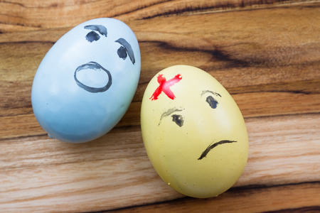 scarred: hand painted easter eggs with sad and scarred expressions on a wooden table