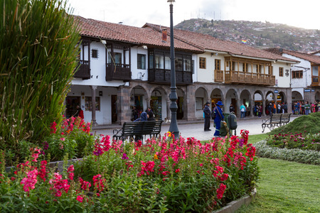 Cusco, Peru - May 13: Beautiful blooming flowers in the Plaza de Armas with colonial buildings in the background. May 13 2016, Cusco Peru.