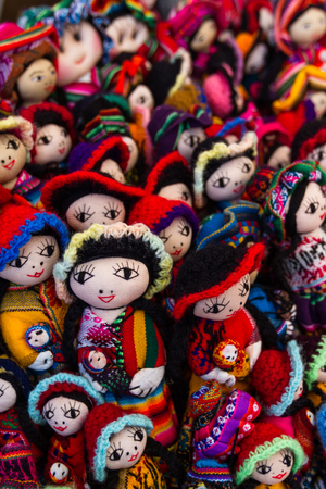 close up of a group pf dolls in a variety of classic Peruvian colors for sale in the Market at Pisac Stock Photo