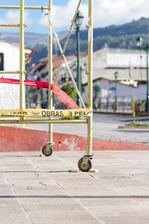 cusco: Cusco, Peru - May 15: Scaffolding on a sidewalk with yellow warning tape as caution in the city  of Cusco. May 15 2016, Cusco Peru.