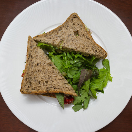 multi grain sandwich: Delicious vegetarian sandwich with sun-dried tomatoes and melted cheese served with a fresh garden salad