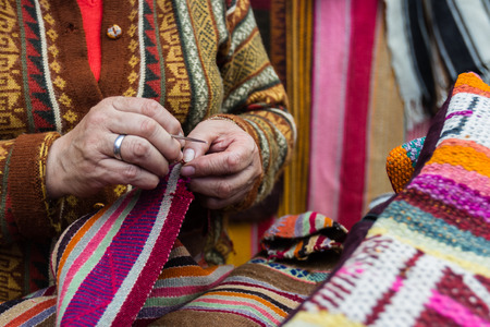 pisac: close up of a womans hands making Peruvian textiles for sale in the market of Pisac